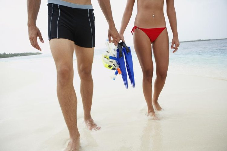 Close-up of couple holding snorkeling gear.