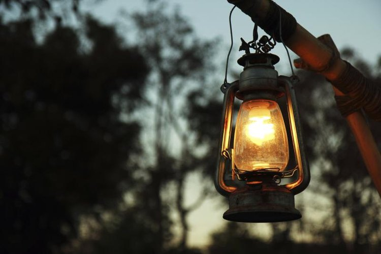 A lantern hanging in fornt of some trees.