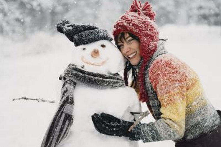 Woman bundled up next to snowman outside.