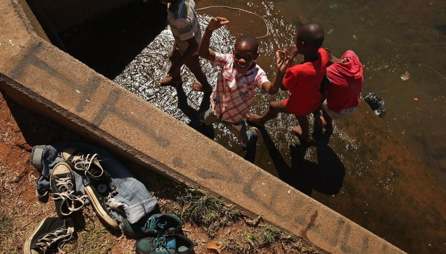 African boys playing in a river with donated jeans and sneakers on the bank.