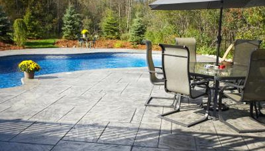 Installing a concrete patio between your home and pool provides a clean surface for swimmers to walk on.
