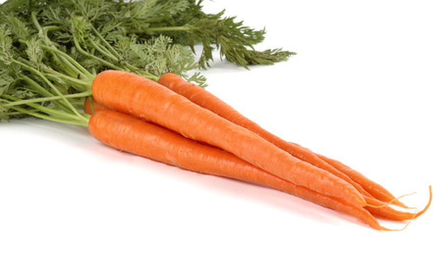While chlorophyll gives the carrots' leaves their green appearance, caroteniods give them their orange color.