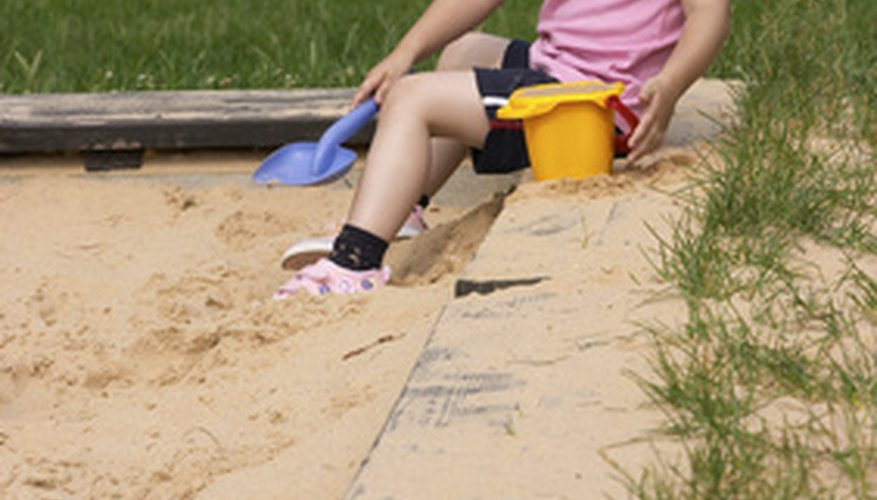 Amend the soil to plant grass in a sandbox.