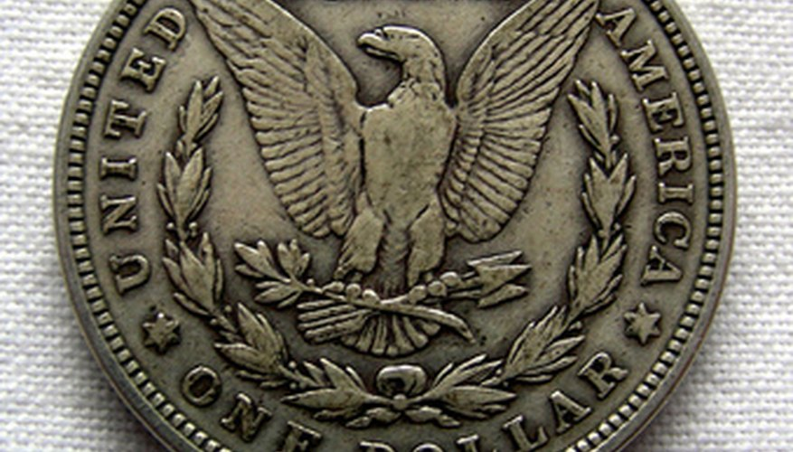 The eagle on the reverse of the Morgan silver dollar clutches arrow and olive branches.
