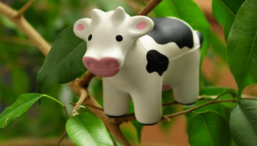 A toy cow inside a rubber plant.