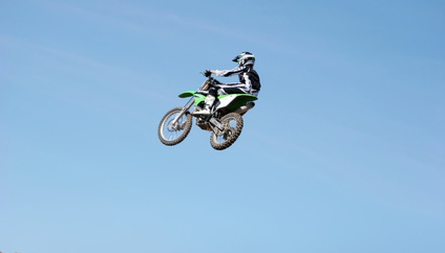 A dirt bike rider grabs some air after jumping a large ramp.