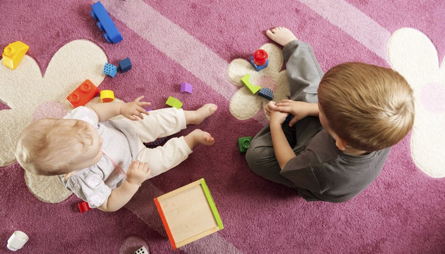 Young siblings playing with blocks together on the rug.