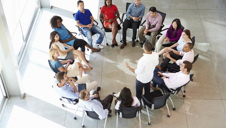 An overhead view of a group of office employees sitting in a close circle.