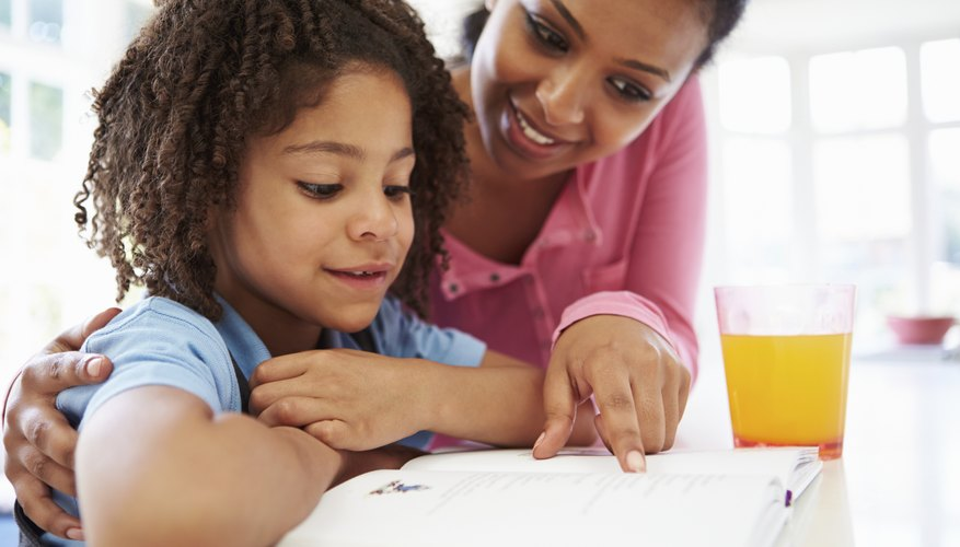 Mother helping child with homework at table