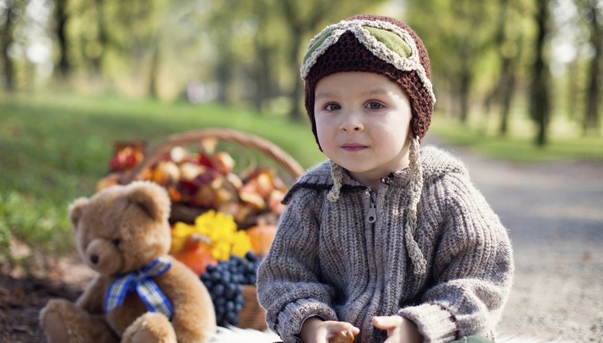A portrait of a little boy at a teddy bear picnic in the park.