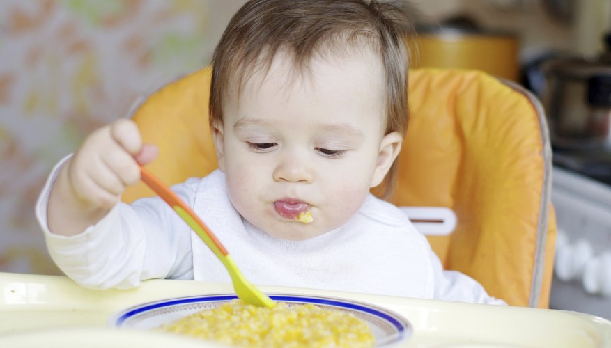 A 1 year old baby eating with a spoon.
