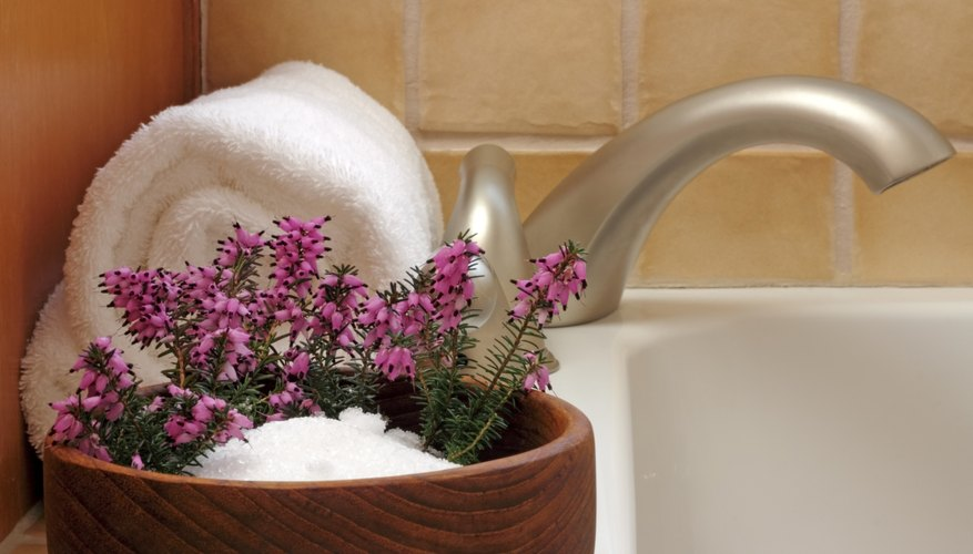 Epsom salt in a bowl with flowers next to a bathtub.
