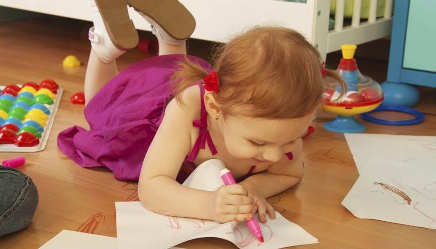 A two-year-old girl uses paper and washable markers.