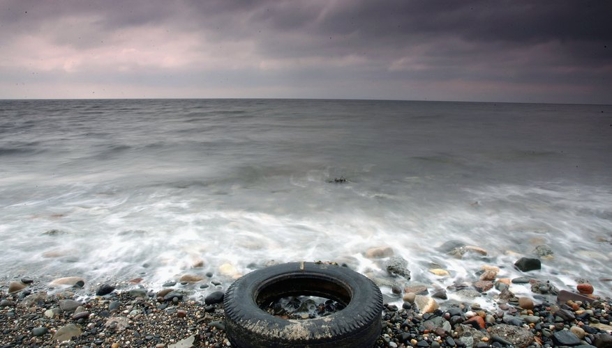 Old tire rests on the coastline in England