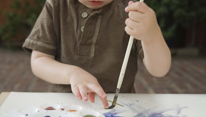 Holding a paintbrush encourages fine motor skill development.