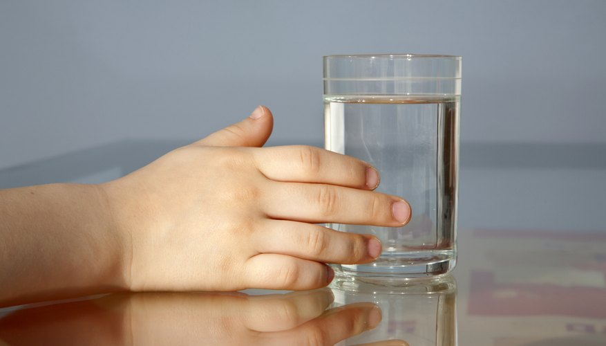 A child touches a glass of water.