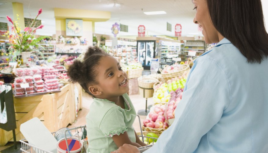 A mother talking to her young daughter at the grocery store.