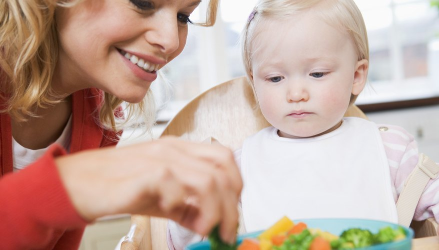 Mom feeding baby vegetables