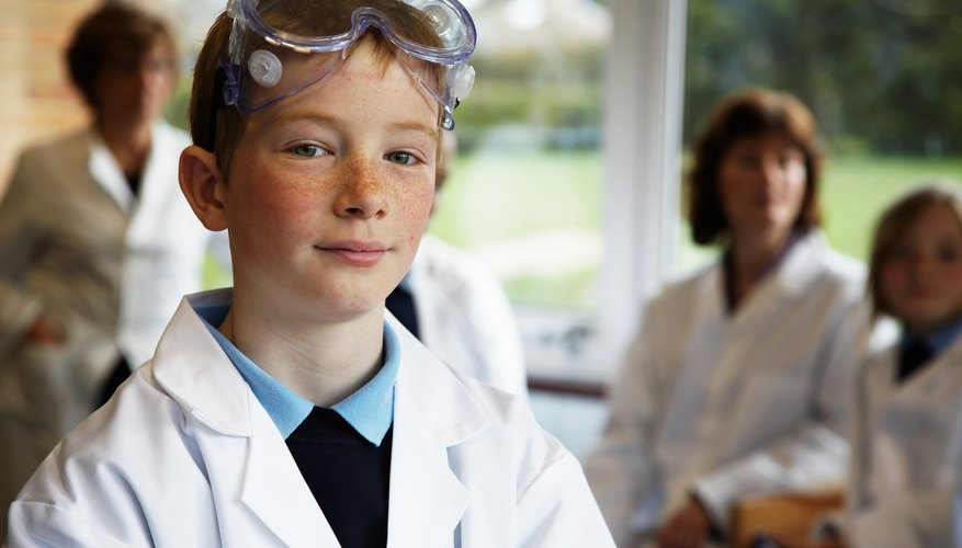 Young boy with lab coat and goggles in science class.