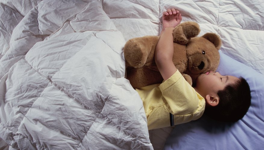 Young boy sleeping in bed with a teddy bear.