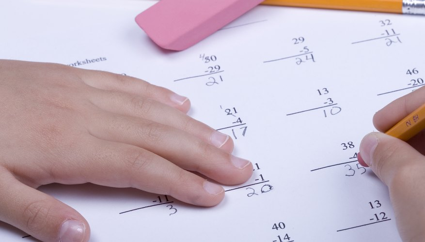 A close-up of a child working on subtraction math problems.