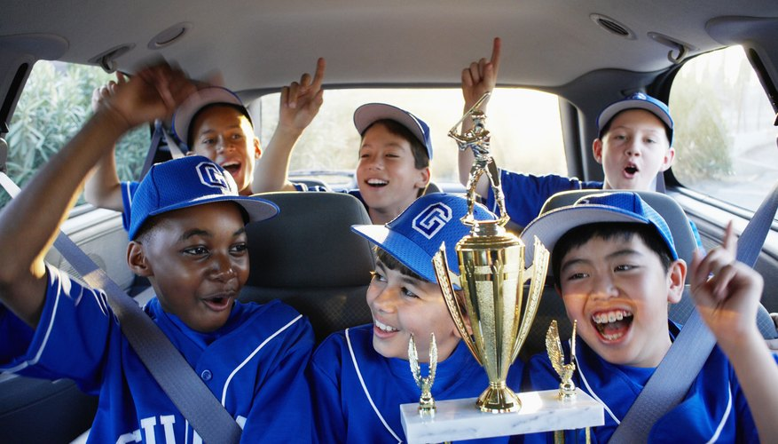 Boys on a little league team celebrate a winning game in a SUV.