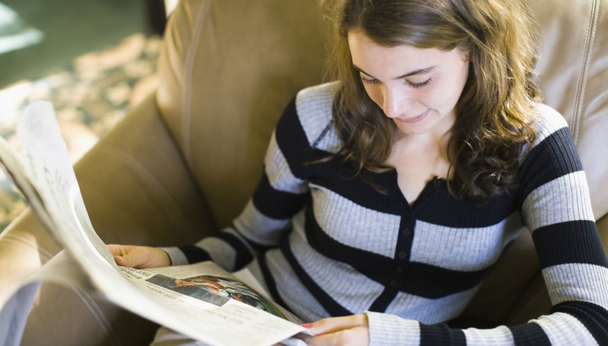 Teenage girl reading a newspaper.
