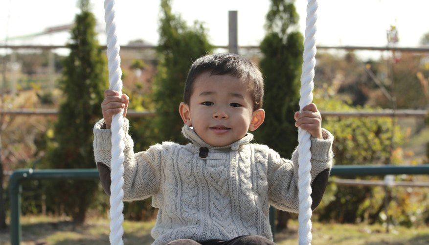 A three-year-old toddler on a swing in the park.