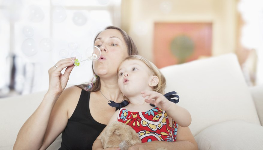 Mother blowing bubbles with two year old in her lap.