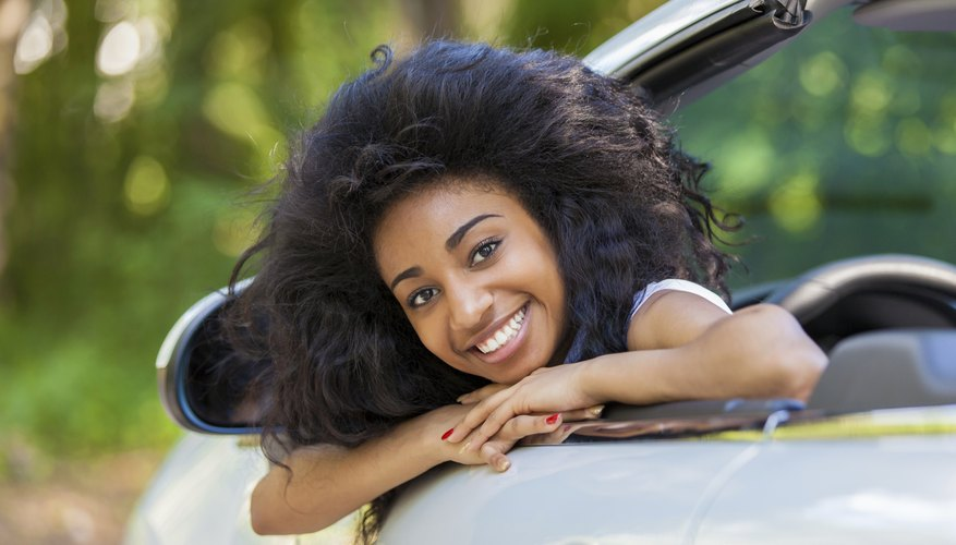 A teenage girl sitting in the driver's seat of a convertible.