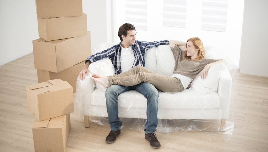 A couple is sitting in their living room by their stuff.
