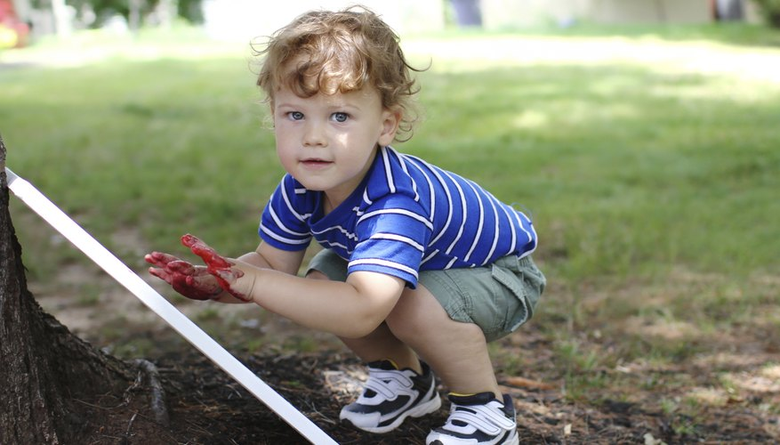 A two-year-old boy makes a finger painting on a canvas in the backyard.