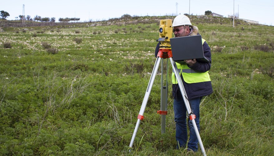 An engineer uses a theodolite on a grassy field