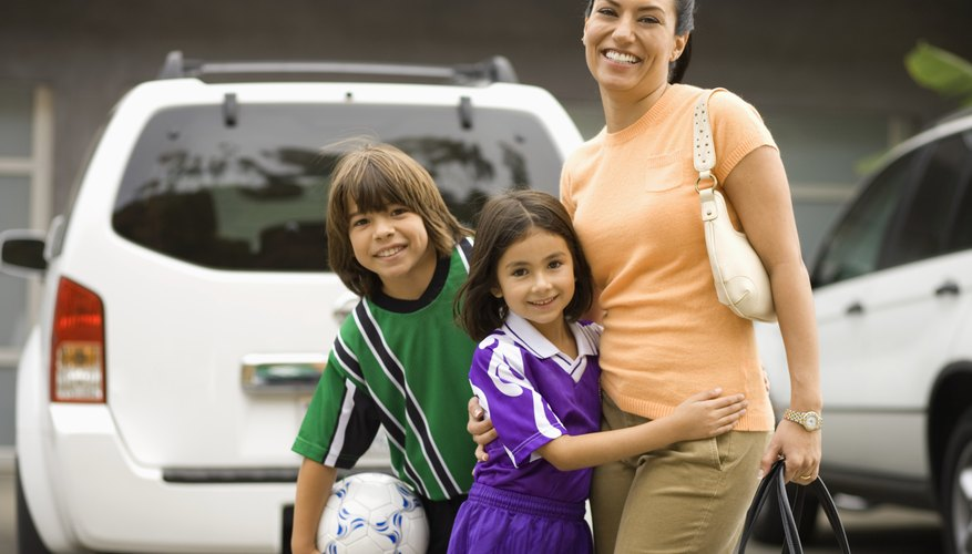 Two children dressed in soccer uniforms hug their mom in a parking lot.