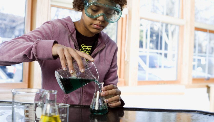 A student pouring liquid into a beaker in a science classroom.