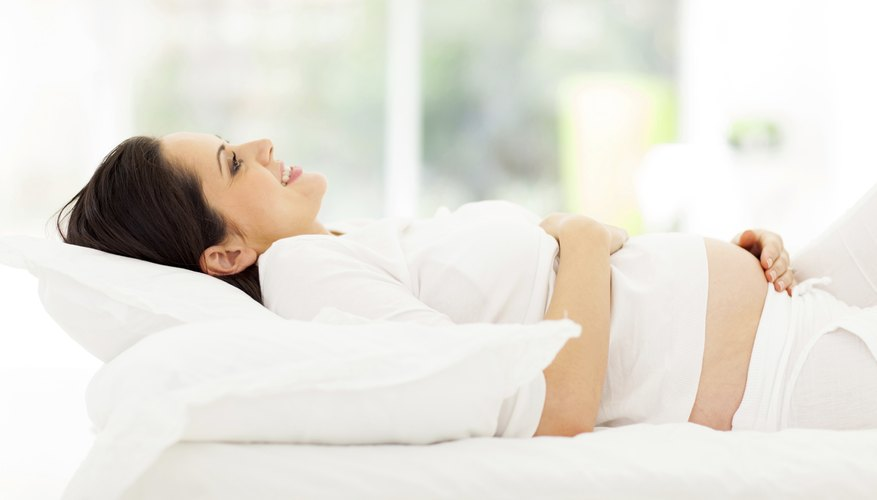 Pregnant woman laying on bed.