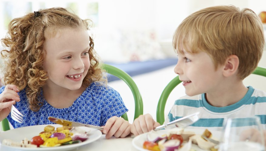 Two young children smiling at each other during breakfast