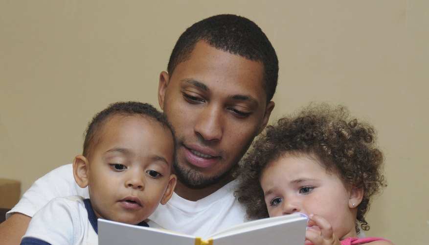 A father reading a book to two toddlers.
