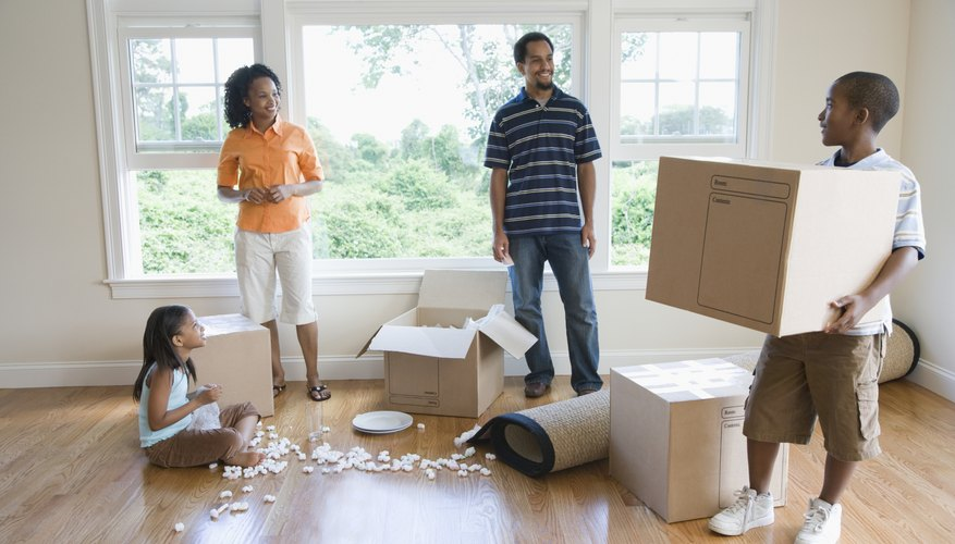 A family is holding moving boxes.