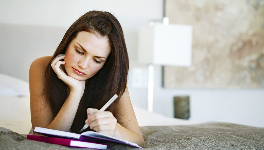 woman writing down notes on her menstrual cycle