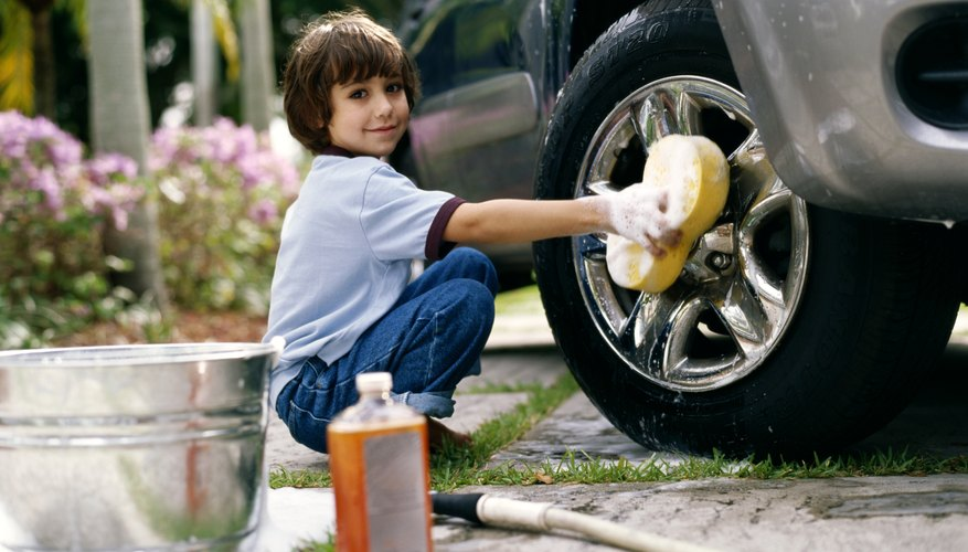 Child washing tires of car.