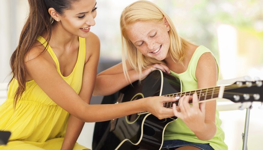 Young teen taking guitar lessons