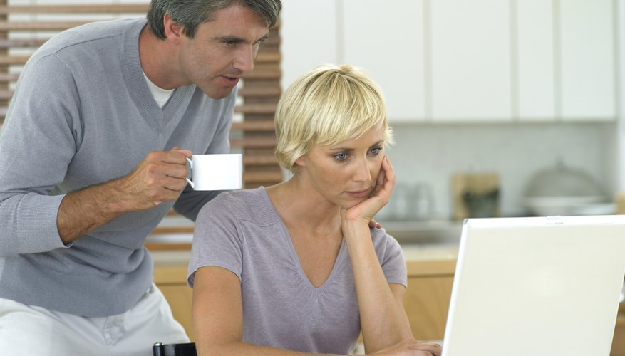 Woman working on laptop in kitchen with husband looking over her shoulder