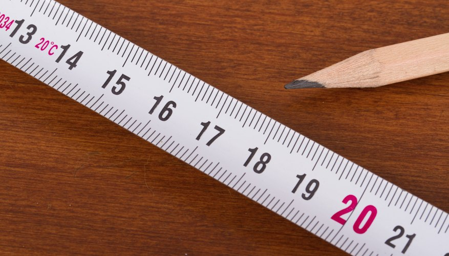 Close-up of measuring tape beside pencil