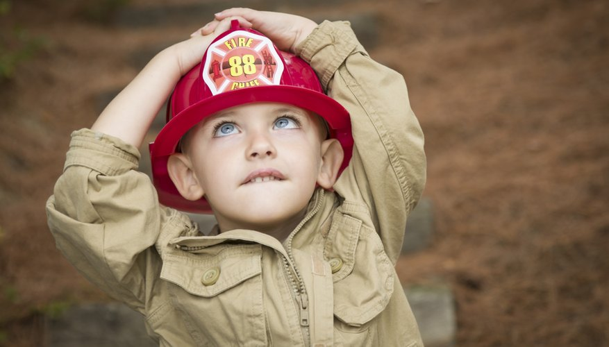 A little boy dressed as a fireman looking up at a tree.