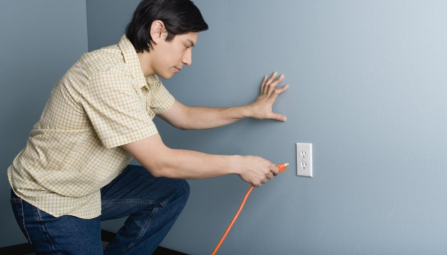 Man plugging a cord into an outlet