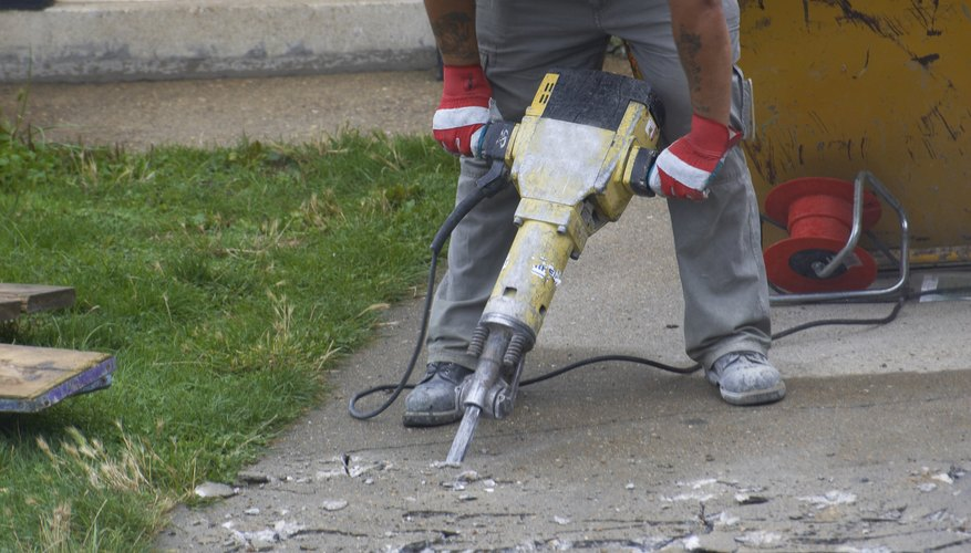 Loud, rapid impacts of metal on stone make the percussive noise of a jackhammer.