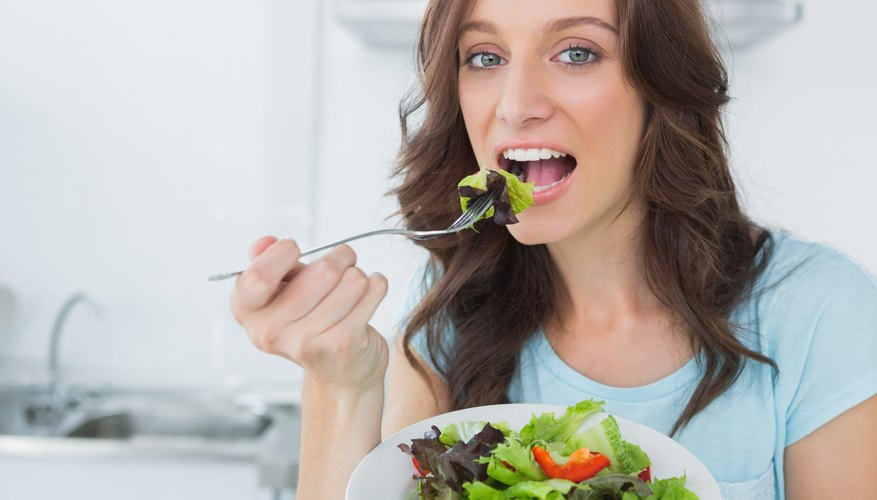 Young woman taking a bite of her salad.