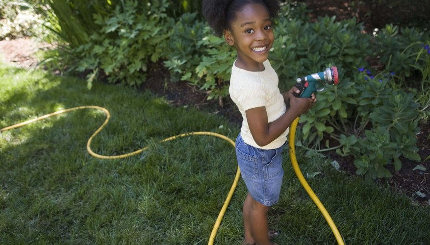 A young girl waters the yard with a hose.