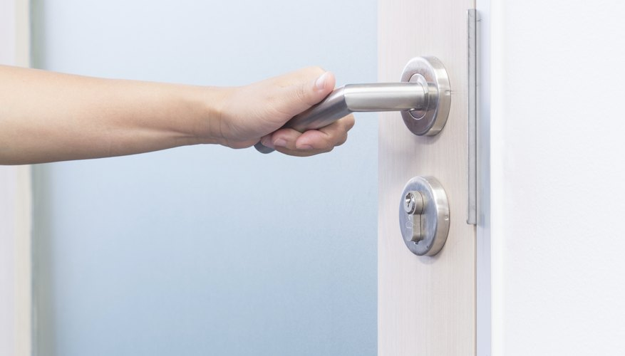 A woman grabs a door handle.